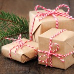 Group of three Christmas presents wrapped in brown paper and ties with a festive red and and white baker's twine on dark wooden background