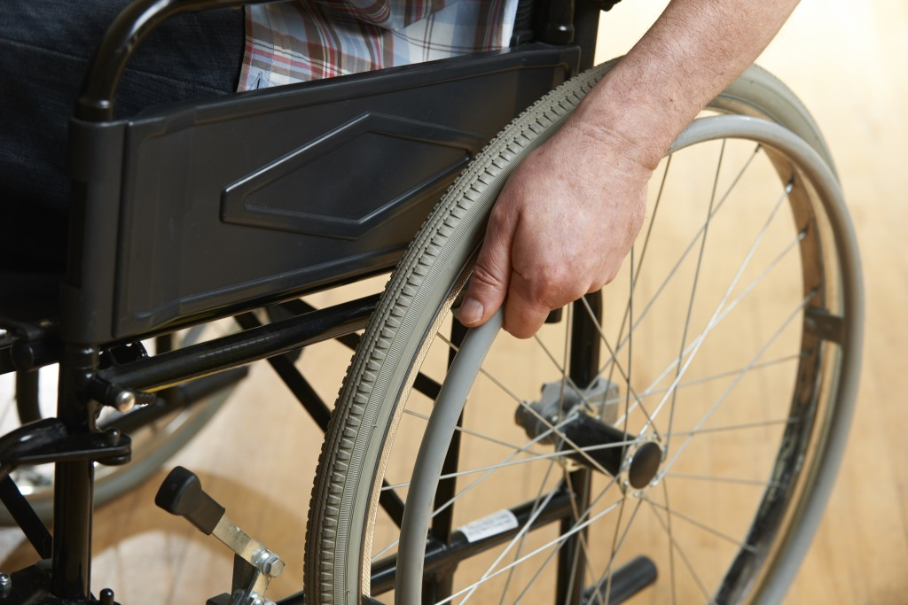 Close Up Of Man's Hands Pushing Wheelchair