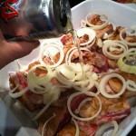 Beer Braised BBQ Ribs layers in baking dish with onions